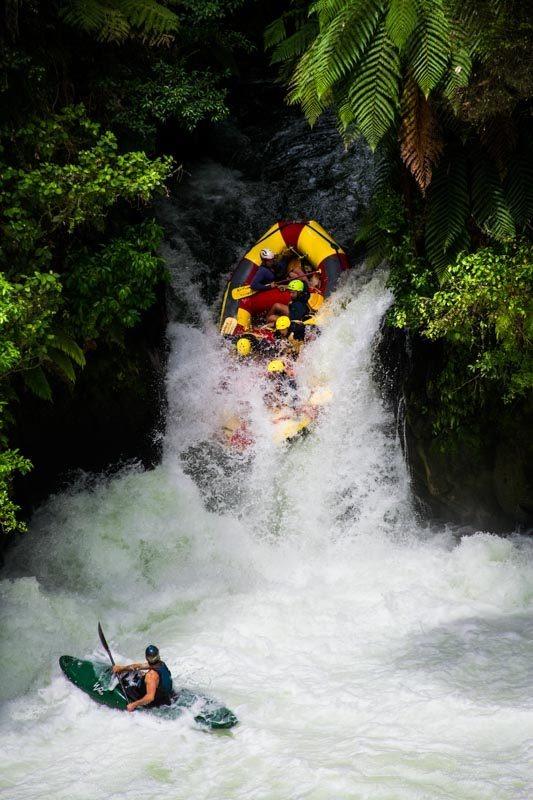 Zachranář pod vodopádem dohlíží na bezpečný průjezd přes Tutea Falls.