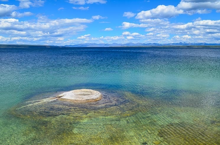 Yellowstone Lake is a lovely area. There is a Fishing Cone Geyser in the photo.