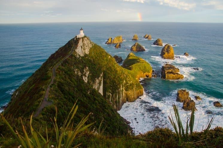 Západ slunce na Nugget Point Lighthouse, jižní ostrov, Nový Zéland