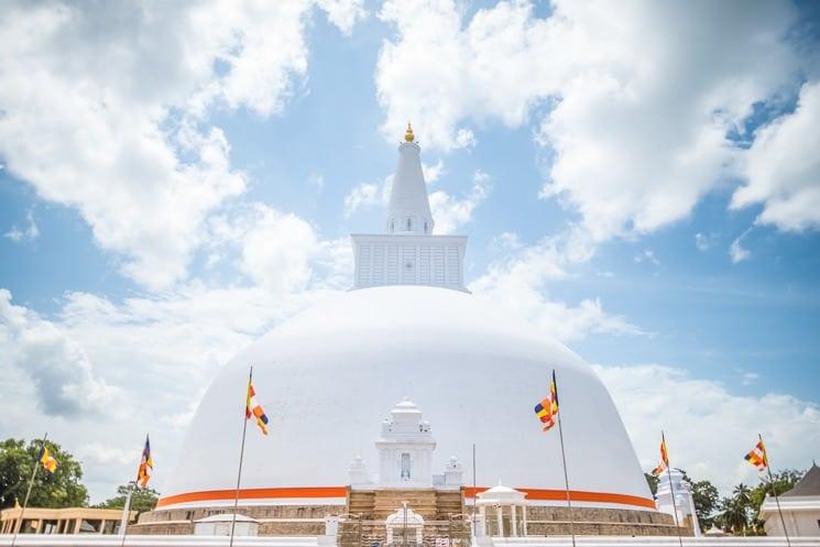 zděný plot okolo 2. největší stupy, Anuradhapura, buddhistické vlajky v pozadí , Srí Lanka